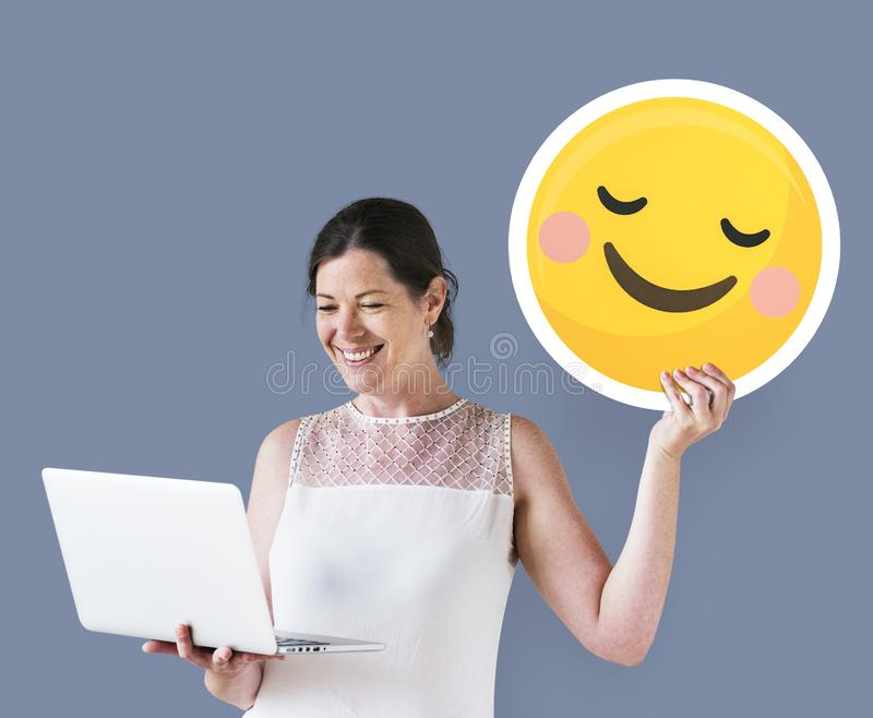 Woman holding a blushing emoticon and using a laptop stock photo