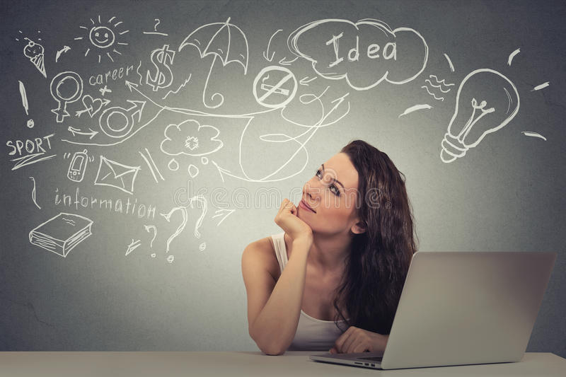 Woman with computer thinking dreaming has ideas looking up stock photography