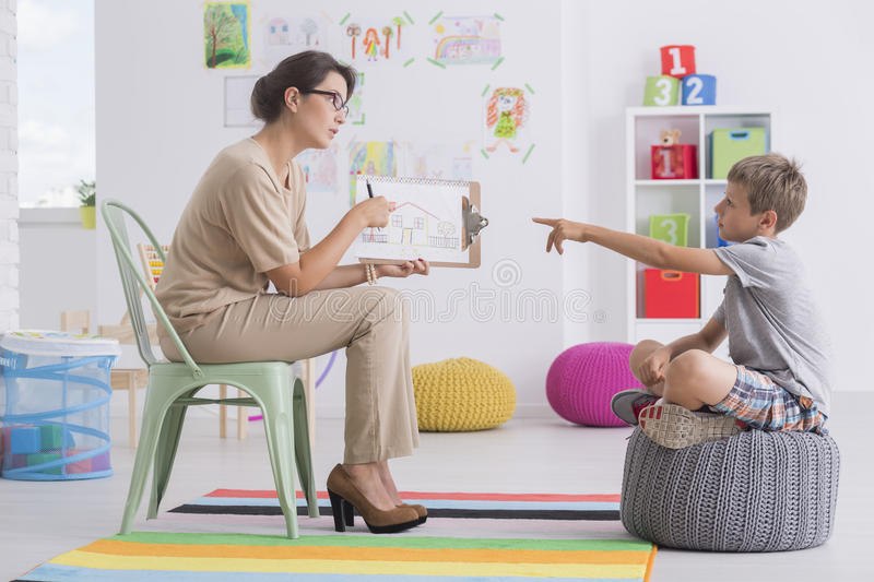Woman conducting child`s psychological test. Young women holding a picture conducting child`s psychological test royalty free stock photos