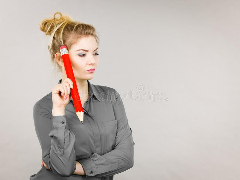 Woman confused thinking, big pencil in hand royalty free stock photo