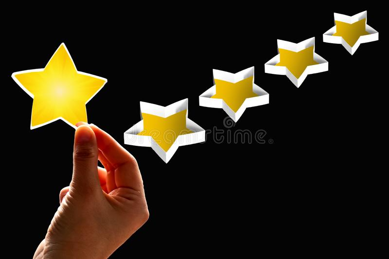 A woman considers gives a first star rating, the concept of a positive rating, reviews and feedback on black. Background stock photos