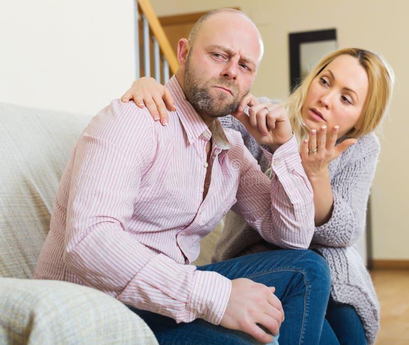 Woman consoling sad men. Sad adult men has problem, loving women consoling him on sofa at home. Focus on men stock photography