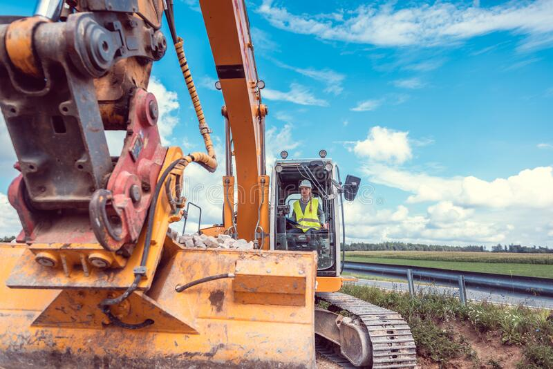 Woman construction worker with excavator on sit royalty free stock image