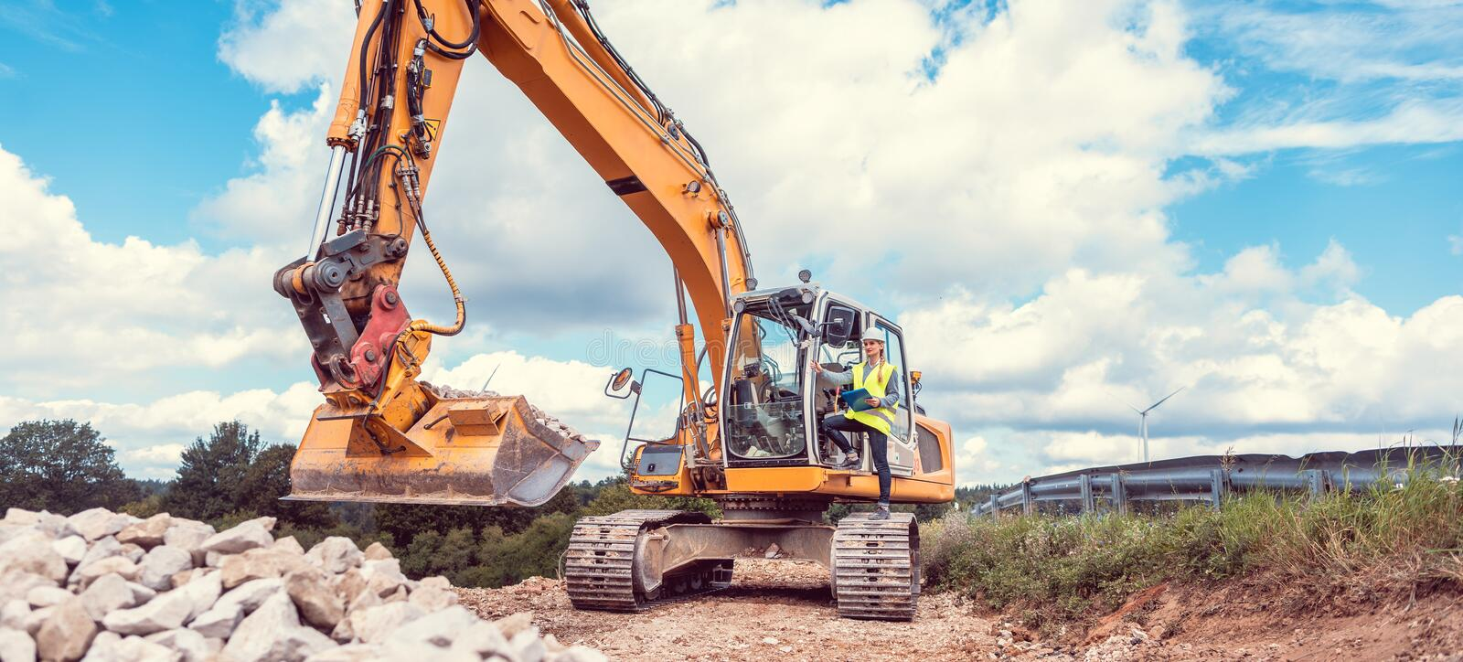 Woman construction worker with excavator on sit stock photography
