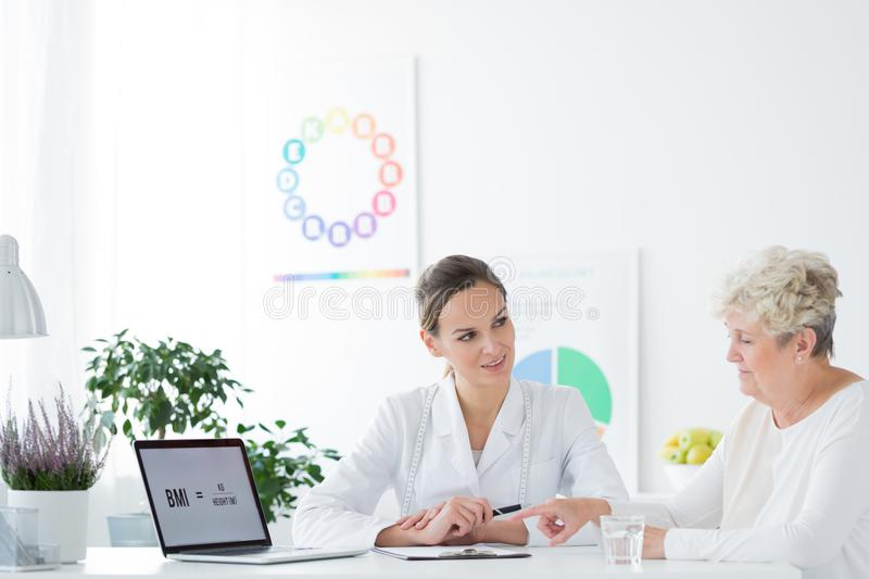 Woman consulting diet with dietitian. Overweight women consulting her diet with professional dietitian stock photography