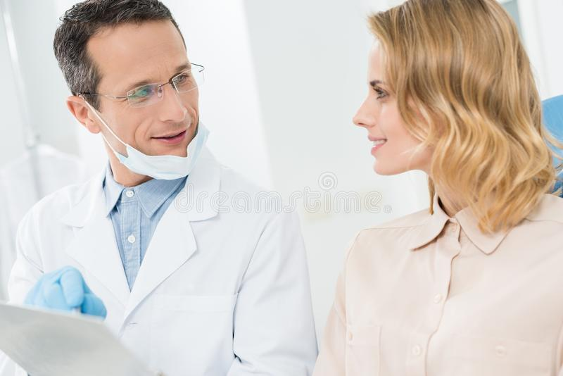 Woman consulting with doctor pointing at clipboard in modern stock image