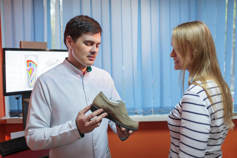 Woman consulting foot doctor royalty free stock image