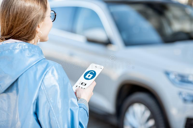Woman controlling car through the smartphone royalty free stock photo