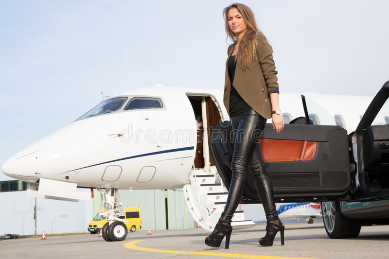 Woman convertable car and corporate private jet. Woman leaving convertable car and corporate private jet royalty free stock images