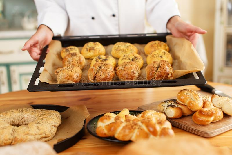 Woman cook with baked goods. Woman hands holding baking tray with homemade baked goods stock photo