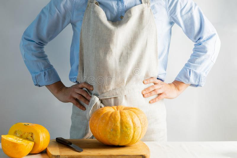 Woman cook or housewife a linen apron hands the belt ripe pumpkins the kitchen table. Organic food concept. Hygge style. royalty free stock photo