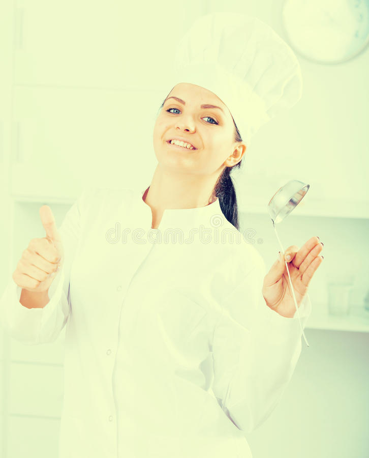 Woman cook with metal scoop. Woman cook holding in hands metal scoop royalty free stock photography