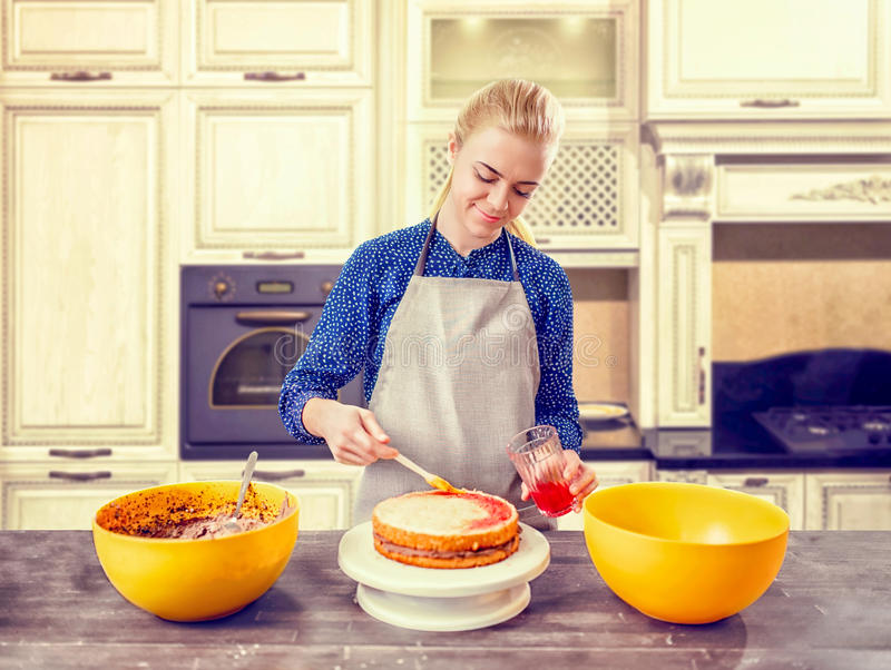 Woman cook smears baked cake with berry syrup. Woman cook smears baked cake with berry jam. Tasty dessert homemade cooking stock images