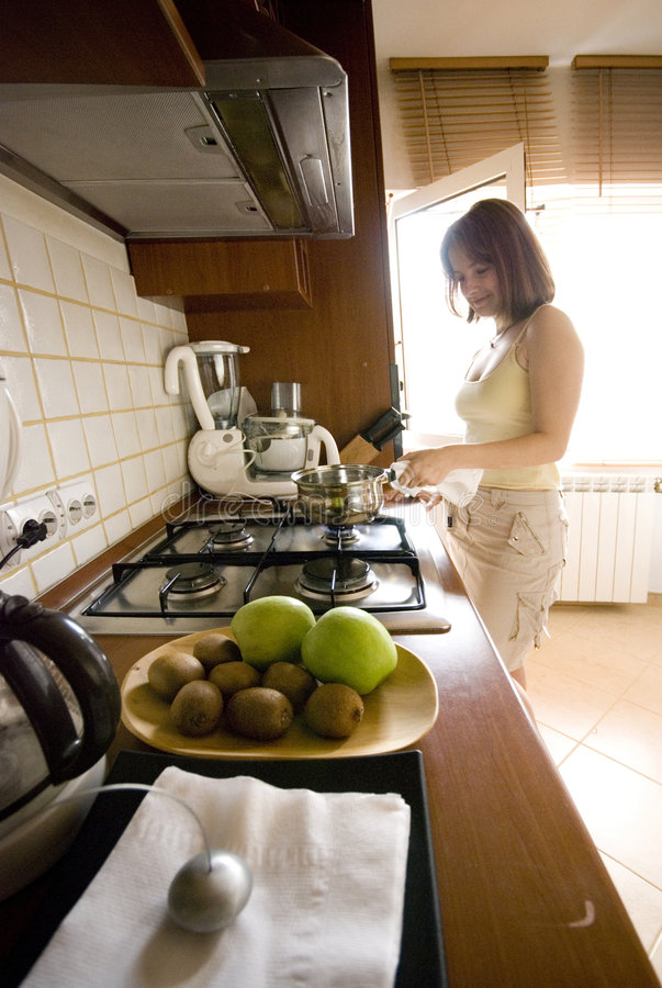 Woman Cooking. Young woman in a modern kitchen at the stove, cooking stock photo