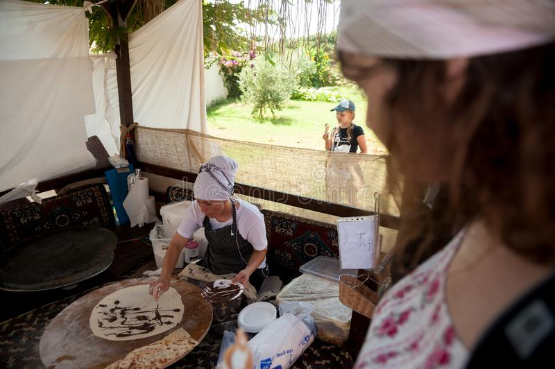 Woman cooking cakes gozleme. Hotel in Turkey. Turkler, Turkey - July 27, 2018: Senza hotel tent. Turkish woman makes a traditional national dish - a baked flat royalty free stock images