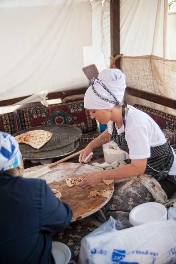 Woman cooking cakes gozleme. Hotel in Turkey. Turkler, Turkey - July 27, 2018: Senza hotel tent. Turkish woman makes a traditional national dish - a baked flat stock images