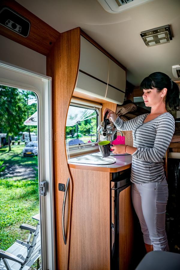 Woman cooking in camper, motorhome interior RV. Woman cooking in camper, motorhome interior. Family vacation travel, holiday trip in motorhome RV, Caravan car royalty free stock photo