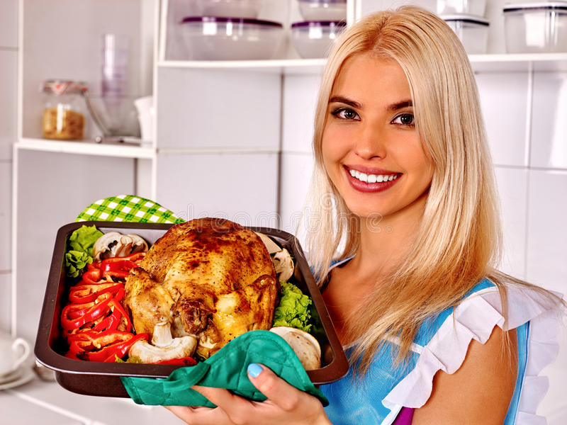 Woman cooking chicken at kitchen. royalty free stock photos