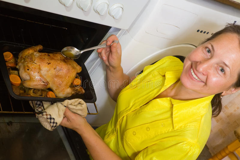 Woman cooking chicken in oven royalty free stock photography
