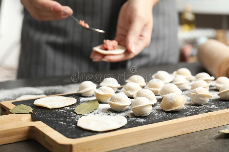 Woman cooking delicious dumplings over grey table. Closeup stock photo