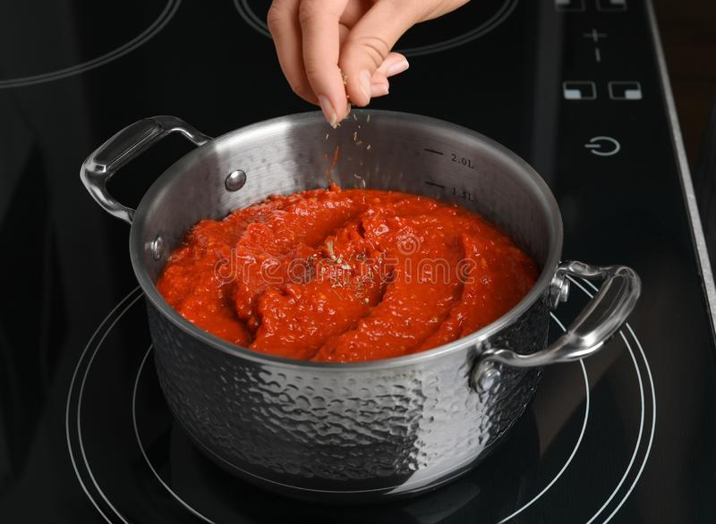 Woman cooking delicious tomato sauce in pan on stove. Closeup stock images