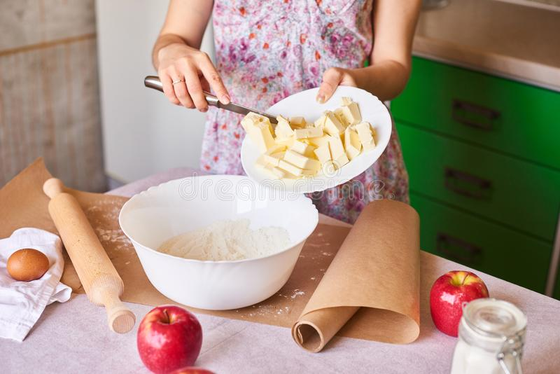 Woman cooking dough for cake, she mixing butter and flour on the bowl on the white table. Woman put ingredients for apple pie into big white bowl. Preparing royalty free stock image