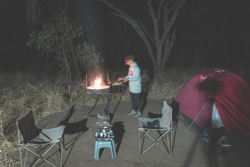 Woman cooking with fire wood and braai equipment by night. Tent and chairs in the foreground. Adventures in african national parks. Toned image royalty free stock photo