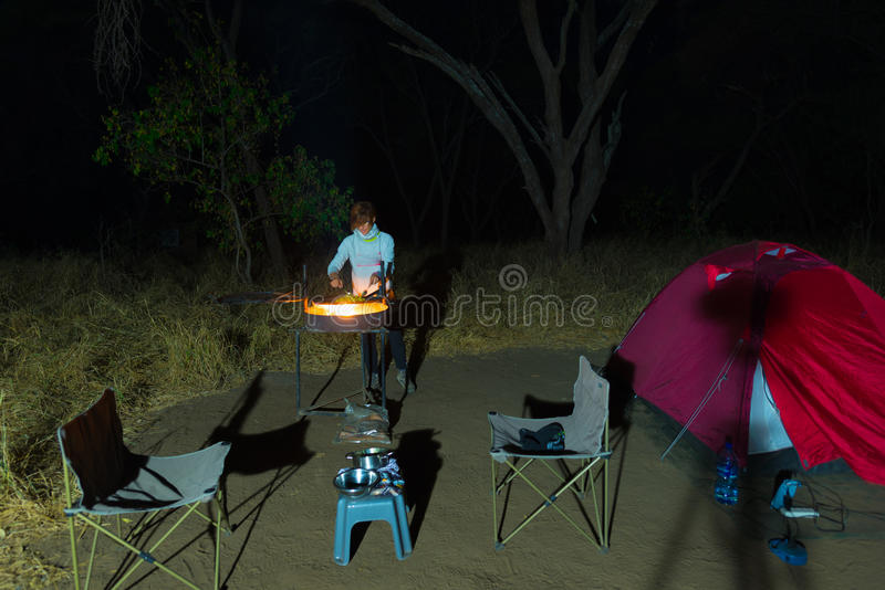 Woman cooking with fire wood and braai equipment by night. Tent and chairs in the foreground. Adventures in african national parks.  stock image