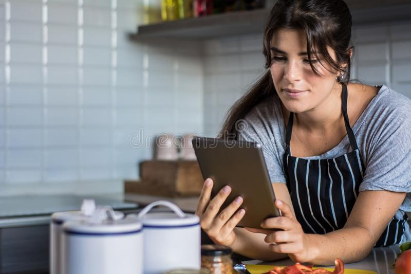 Woman cooking and following recipe on tablet pc royalty free stock photo