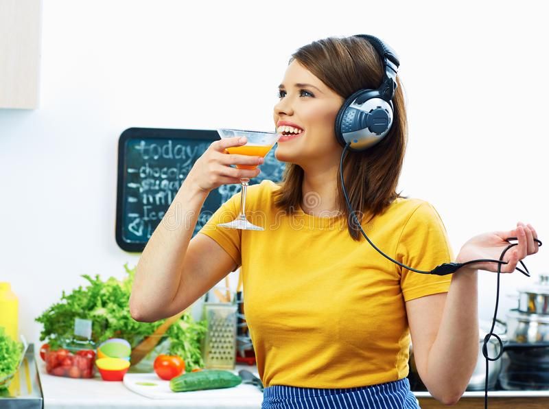 Smiling Girl drinking juice in kitchen and listen music. royalty free stock photos
