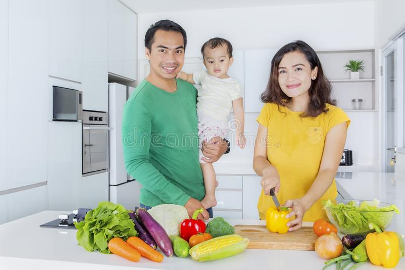 Woman cooking with her husband and daughter stock photography