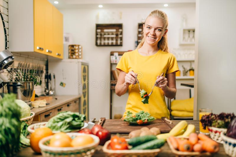 Woman cooking on the kitchen, eco food preparation. Smiling woman cooking on the kitchen, healthy eco food preparation. Vegetarian diet, fresh vegetables and royalty free stock photo