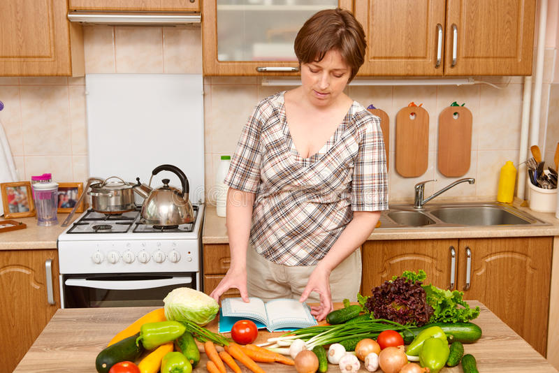 Woman cooking, kitchen interior with fresh fruits and vegetables on the table, healthy food concept royalty free stock images