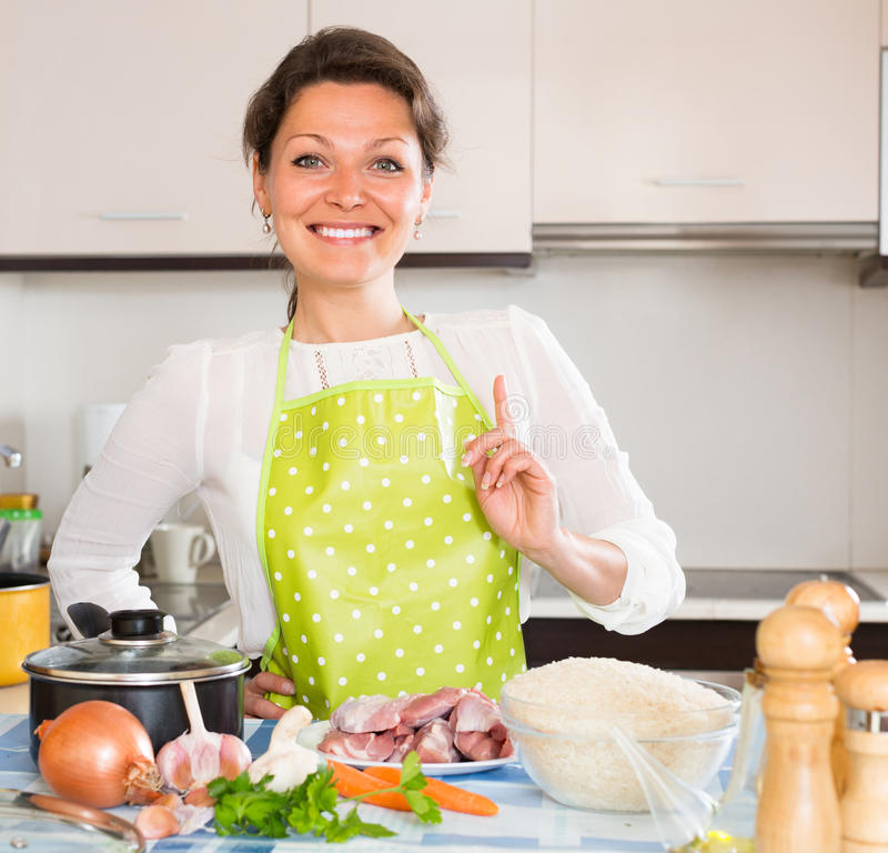 Woman cooking meat with rice stock images