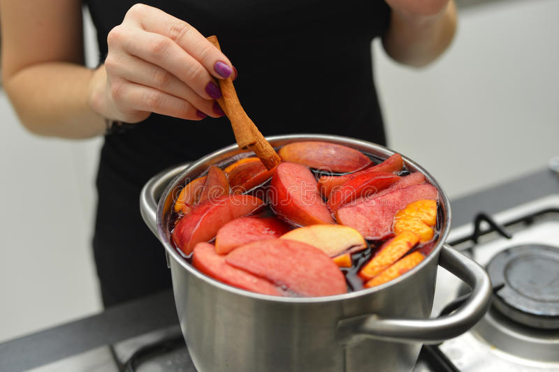 Woman cooking mulled wine at the kitchen stock photo