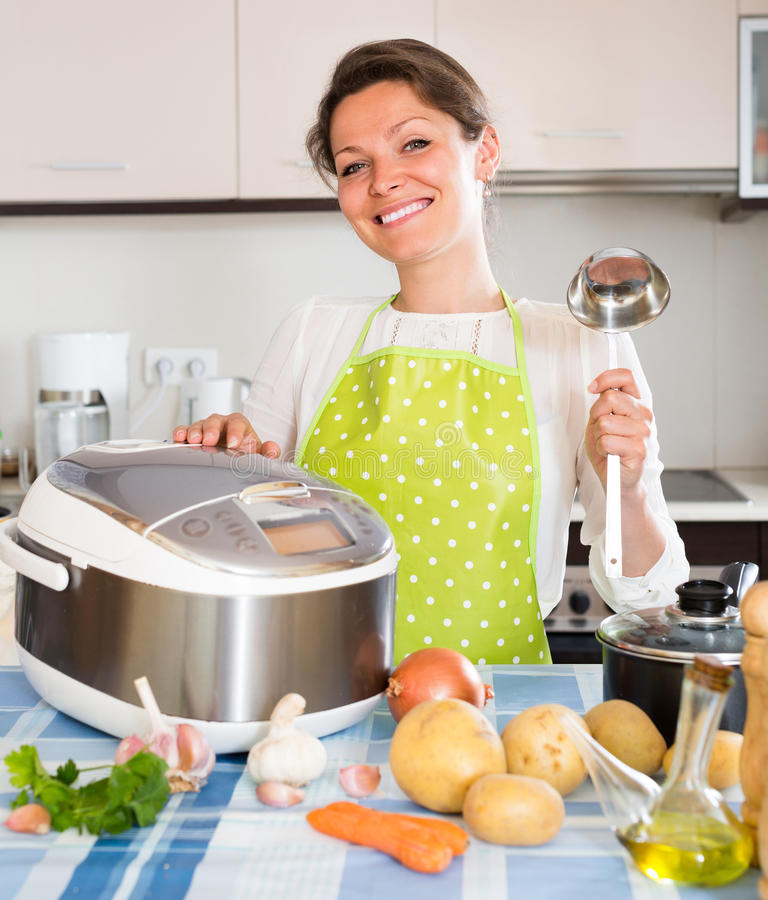 Woman cooking with multicooker royalty free stock photography