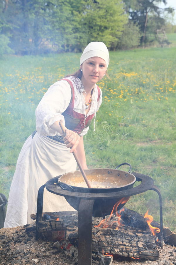 Woman cooking on opened fire. Woman cooking in historical black kitchen with melting kettledrum on opened fire royalty free stock images