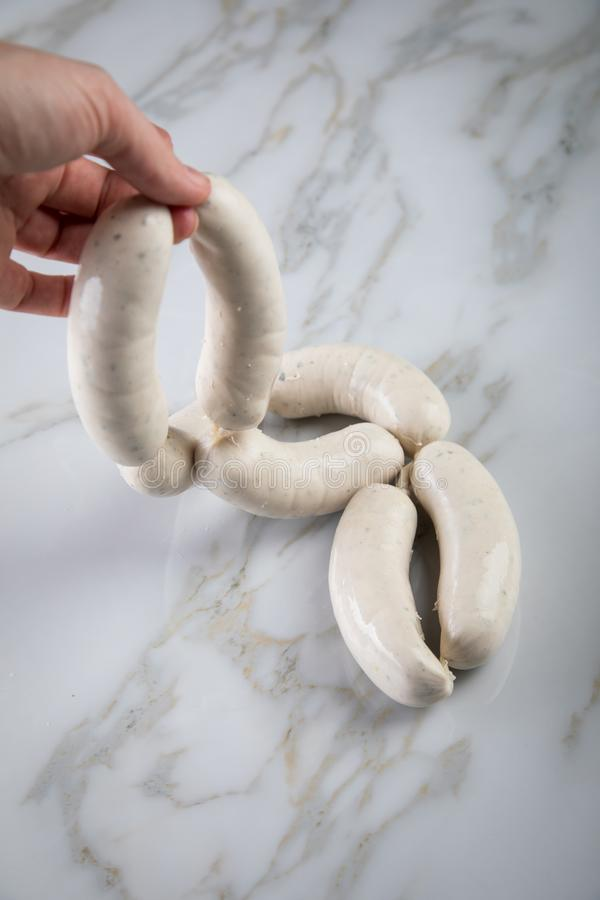 Woman cooking raw German Bavarian Weißwurst white sausage chain of marble background royalty free stock photo