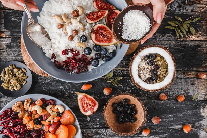 Woman cooking Rice coconut porridge with figs, berries, nuts and coconut milk in plate. On rustic wooden background. Healthy breakfast ingredients. Clean eating stock photo