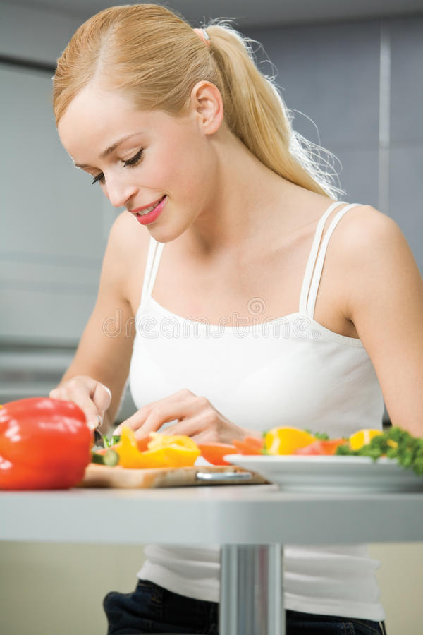Woman cooking salad. At home stock photography