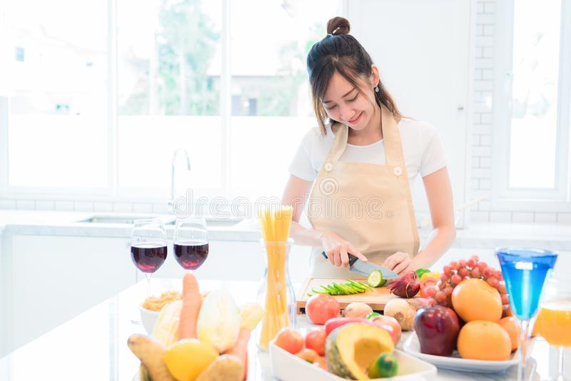 Woman cooking and slicing vegetable in kitchen room with full of food and fruit on table. Holiday and Happiness concept royalty free stock image