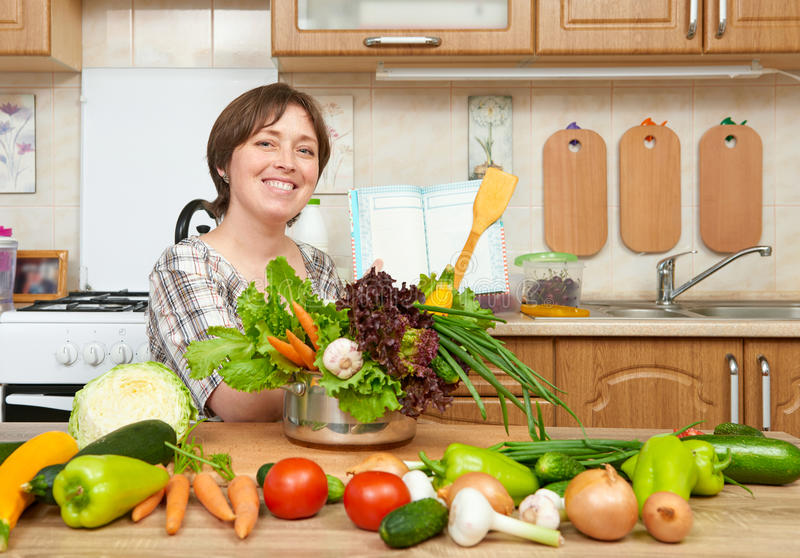 Woman cooking soup from vegetables. Home kitchen interior. Healthy food concept royalty free stock image