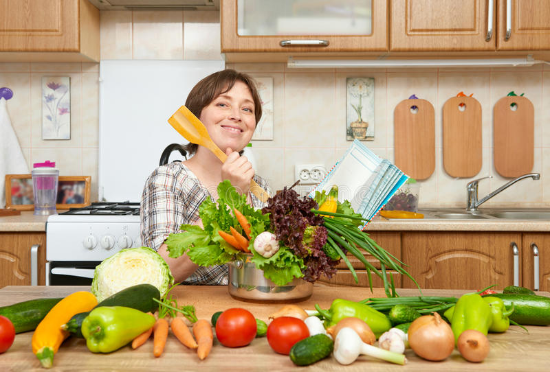 Woman cooking soup from vegetables. Home kitchen interior. Healthy food concept stock photo
