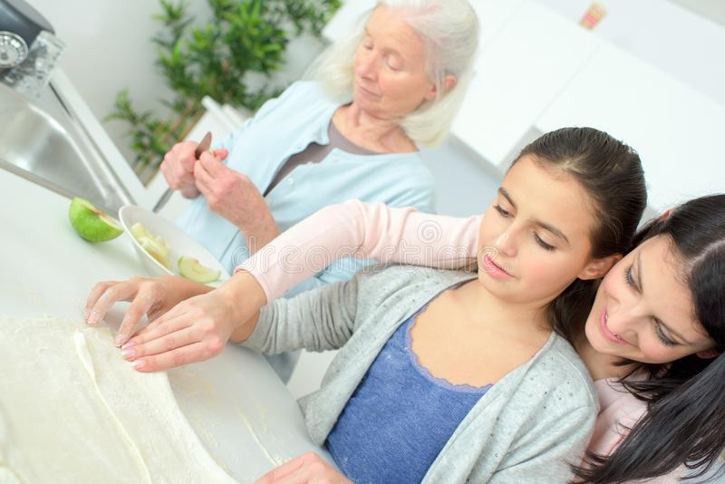 Woman cooking traditional apple pie with daughter and grandmother royalty free stock image