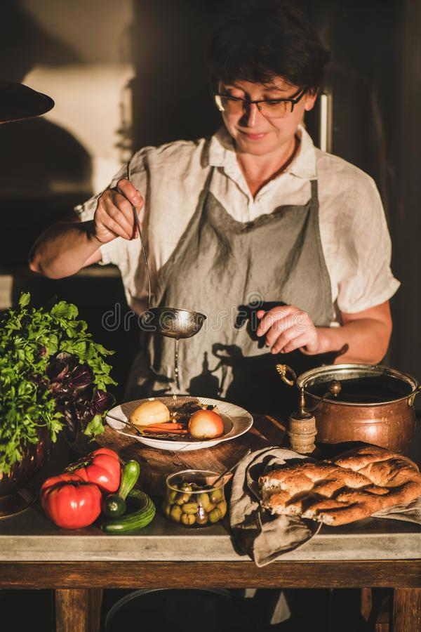 Woman cooking Turkish traditional meat soup Haslama with vegetables royalty free stock images