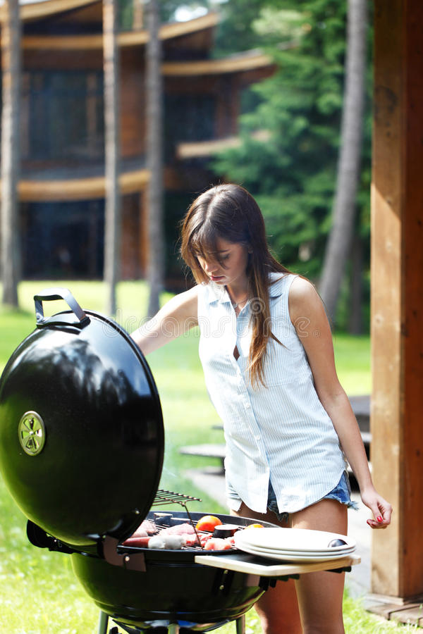 Woman cooks on grill royalty free stock photos