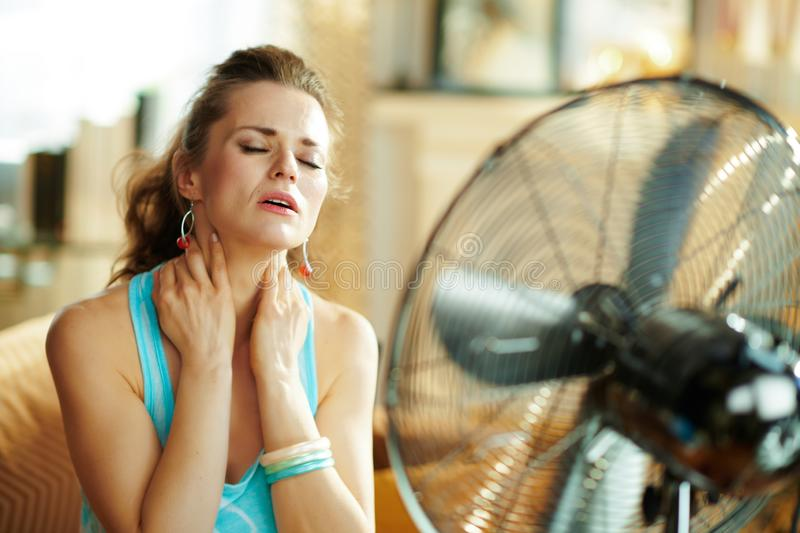 Woman cooling down in front of fan suffering from summer heat stock photo