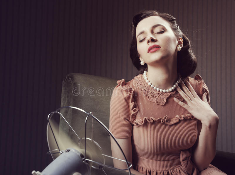 Woman cooling herself with fan. Beautiful woman using a fan to cool off stock images