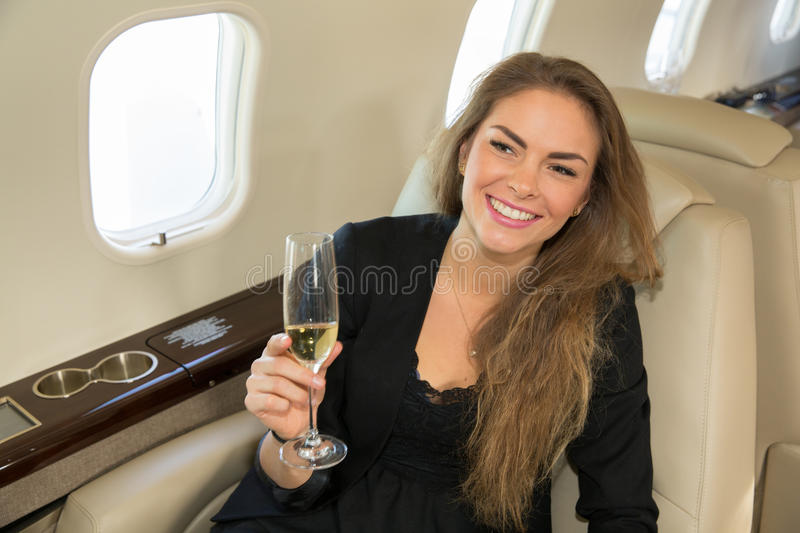 Woman in a corporate jet drinking a glass of champagne royalty free stock photos