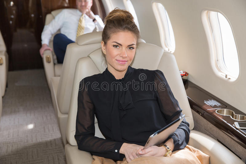 Woman in corporate jet looking to camera stock photography